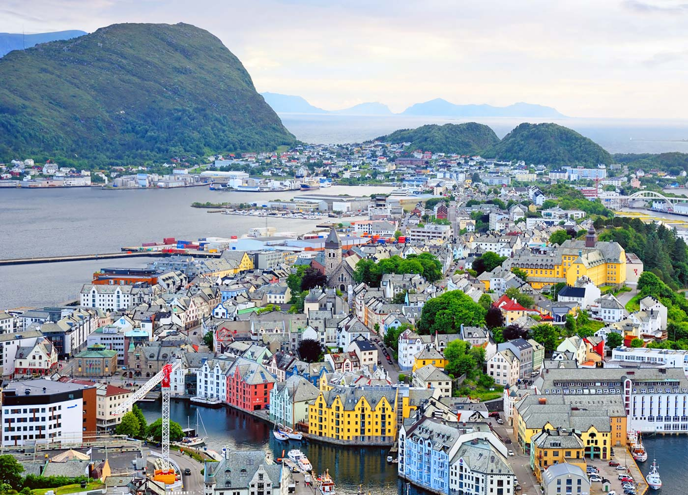 arial view of alesund, norway shows vibrant buildings in between the ocean and beautiful large mountains