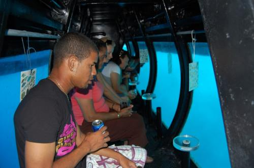 people inside semi-sub looking through windows