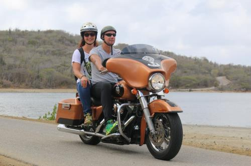 a couple on thier orange Harley Davidson