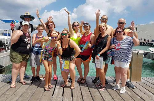 a group of guests smile, wave and give a thumbs up while posing on the docks