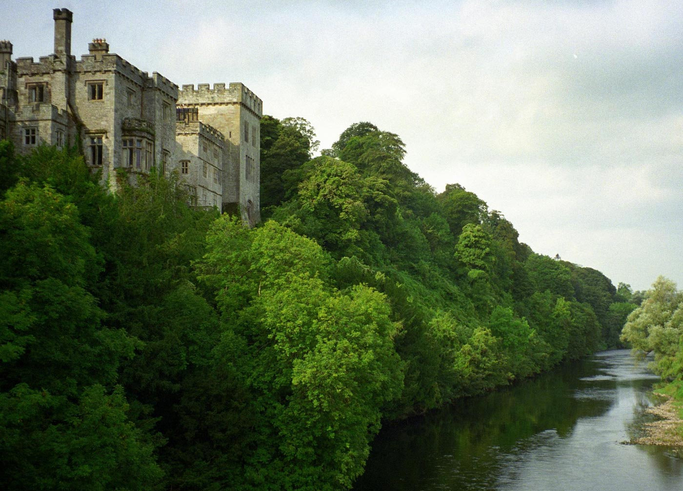 a large stoned castle is surrounded by oversized lush trees and a river
