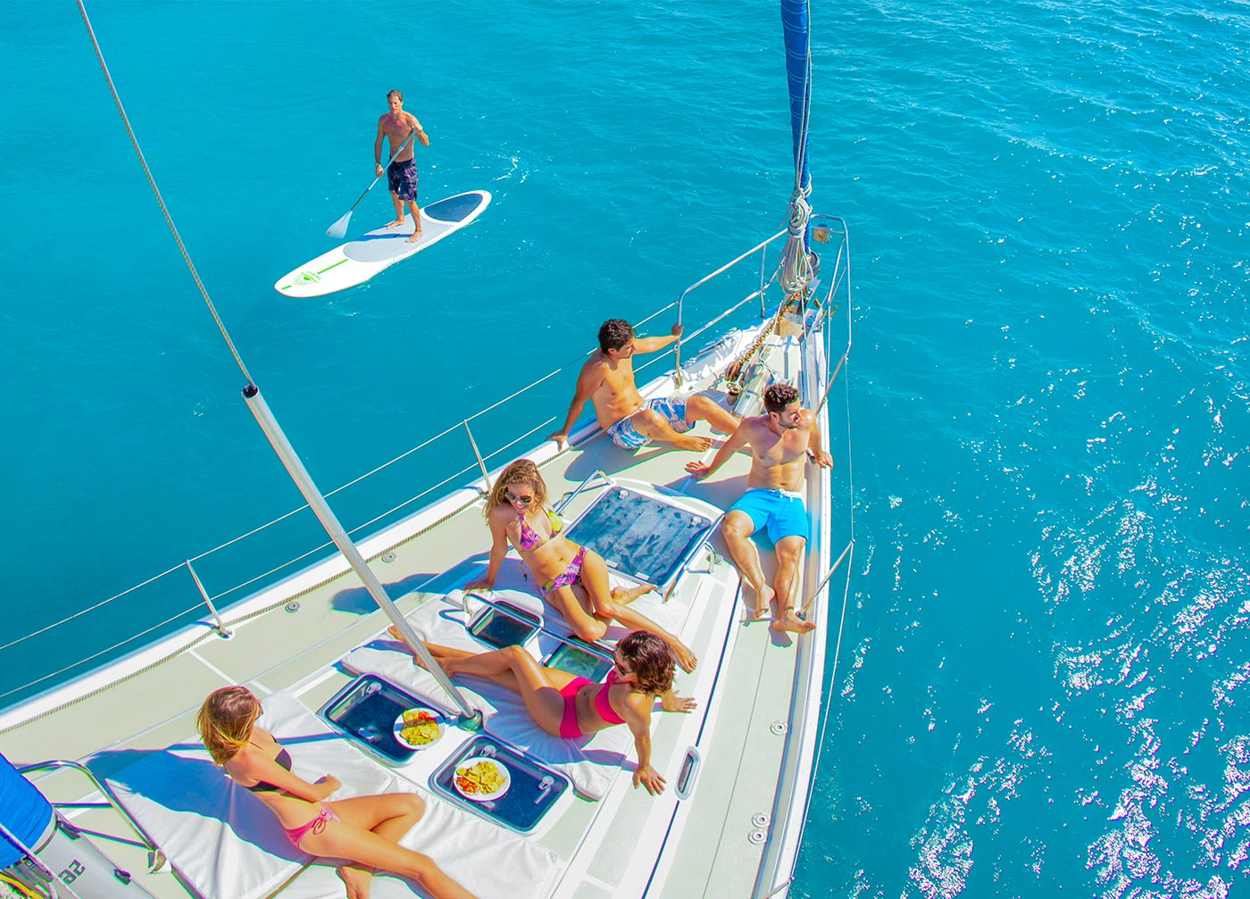 a few guests enjoying the sun on the the sailboat and the paddle board