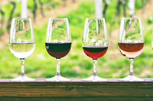 4 glasses holding different types of wines are lined up on a wooden surface at a wine tasting