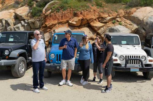 guests stands in front of a set of parked jeeps with wine glasses in hand