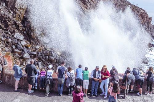 a group of guests watch a large amount of water flow through a blowhole