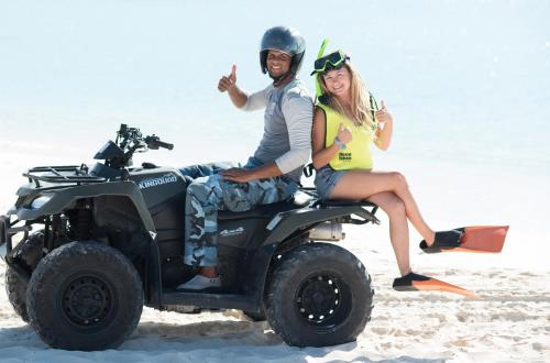 guests gives a thumbs up while sitting on a parked atv
