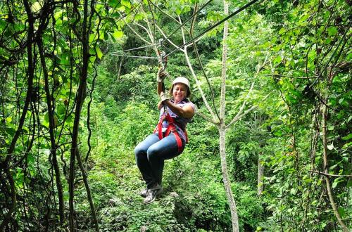 woman zip lining through trees
