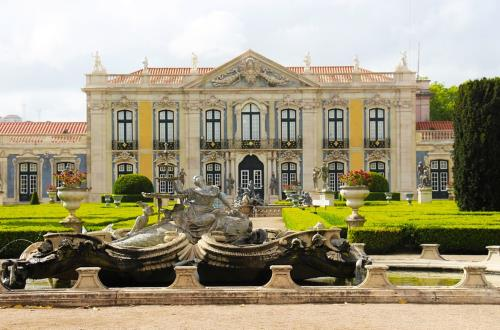 looking past large fountian in gardens of Palace de Queluz towards historic facade of palace