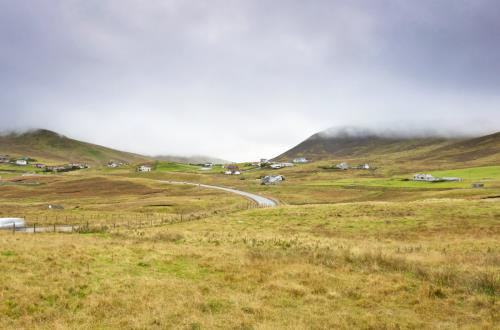 panoramic view of a field in shetland with clouds covering the hills