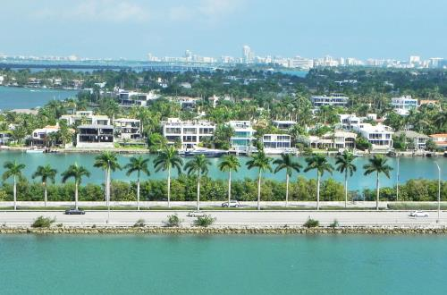 miami mansions are lined up in a row on the water with the miami skyline in the back