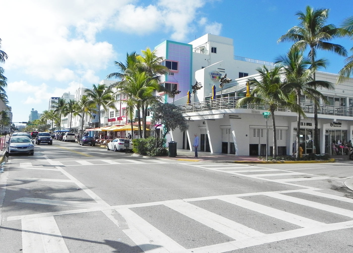 street view of miami's south beach shows bright palm trees and stores along the sidewalk
