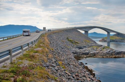 cars are driving up a bridge overlooking a bay in molde, norway