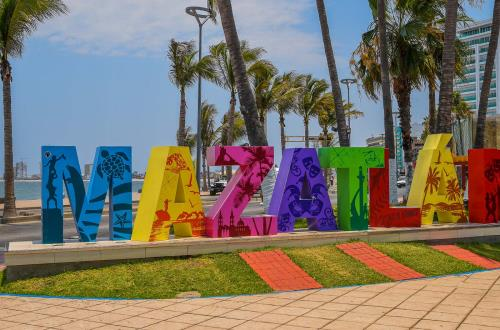 a large colorful sign spelling out mazatlan by the water