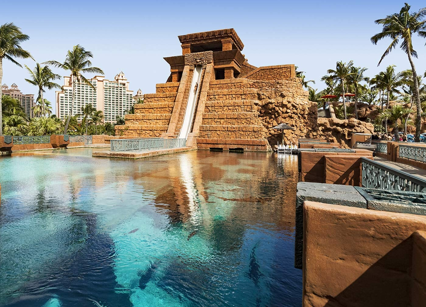 mayan themed design water slide with an aquarium in front filled with marine life