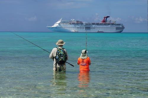 fishermen view carnival cruise line ship out at sea
