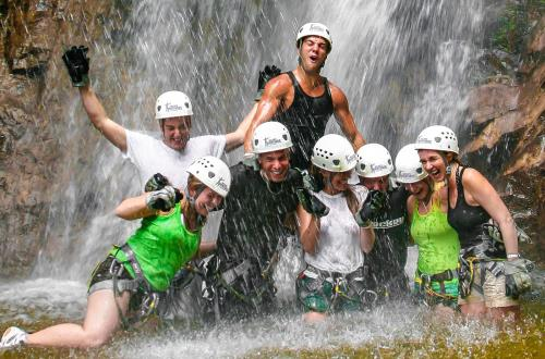 a group of guest smiling and posing for a picture in the water under the waterfall