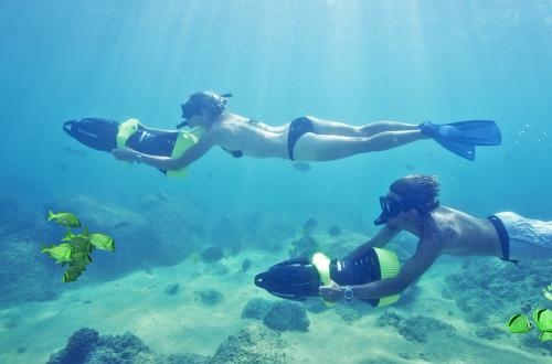 a couple snorkels through the ocean alongside beautiful colored fish while holding on to underwater motor jets