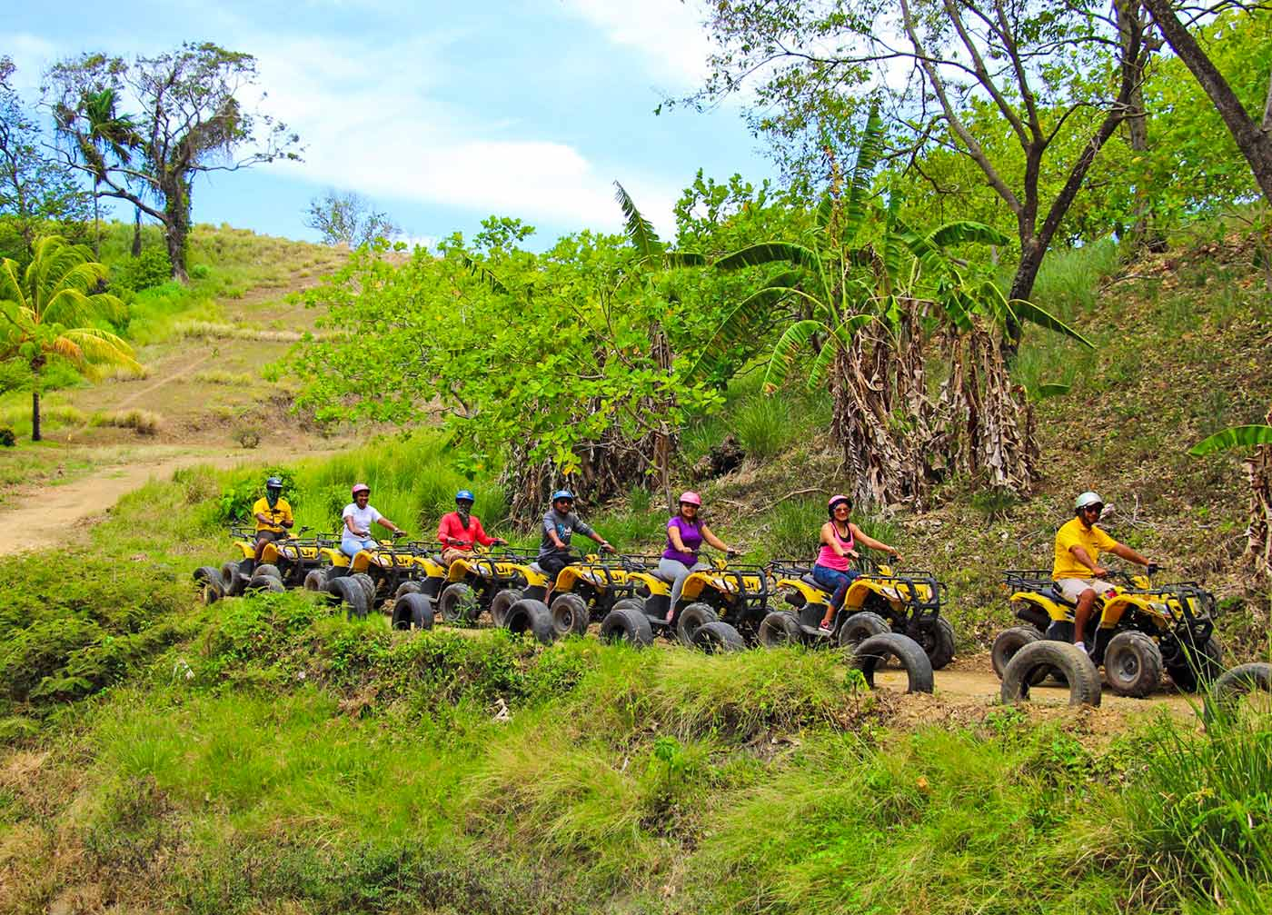 a group of guests driving ATV's on a trail through the jungle