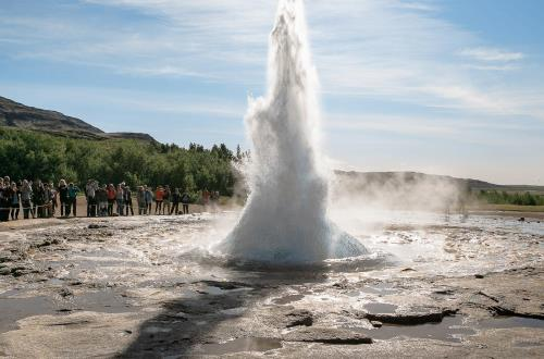 a group of guests watch and take photos as the geyser shoots into the sky