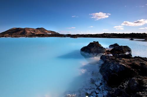 the famous clear blue water of the blue lagoon is vibrant on a sunny day with a mountainous landscape