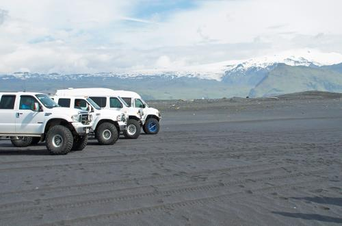adventure trucks line up on the dark sand coast in Ireland in front of a mountain covered in snow