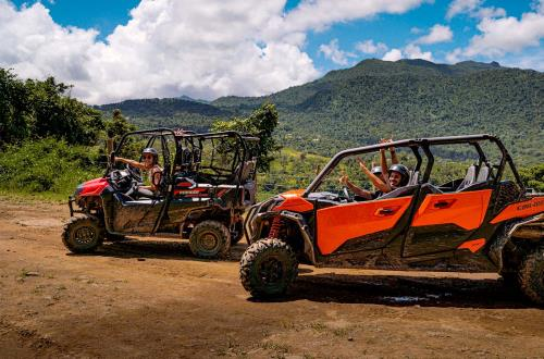 a group of guests smile and wave on their 4x4 off road vehicle