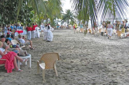 a group of guests gather together on a beach to relax and watch the locals dance