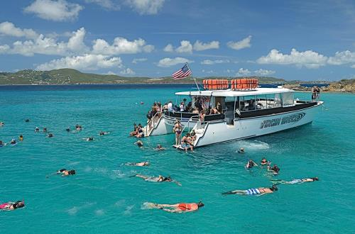 anchored catamaran with guest snorkeling around boat