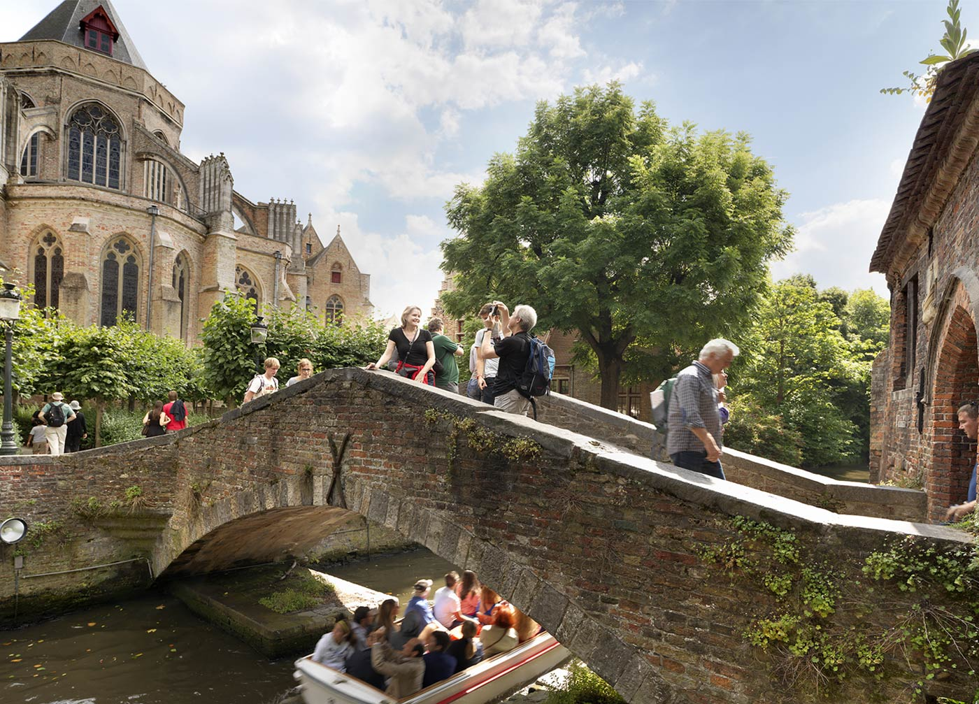 guests walk along an aged bricked bridge while taking photos